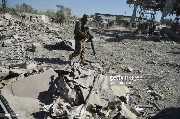 An Afghan security personnel investigates the site of a Taliban car bomb attack in Kabul on July 2 a day after the deadly blast at the Defense...