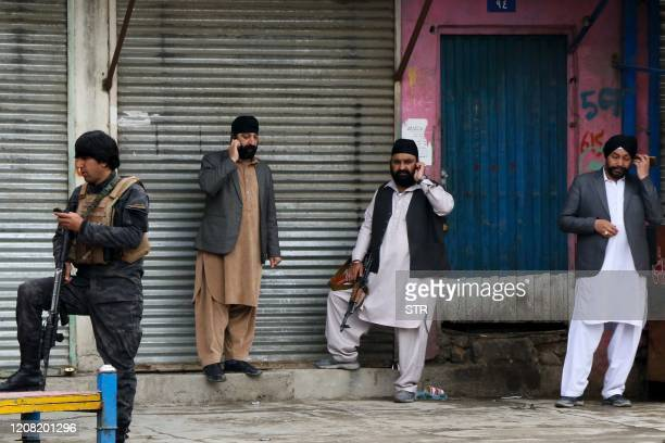 An Afghan security personnel stands along with Sikhs near the site of an attack to a Sikh temple in Kabul on March 25, 2020. - The Islamic State...