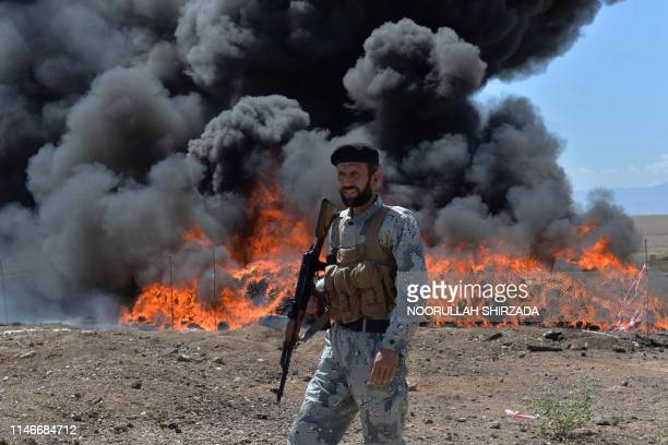 An Afghan security personnel stands guard as seized drugs and alcoholic drinks burn on the outskirts of Jalalabad in eastern Afghanistan on May 28,...