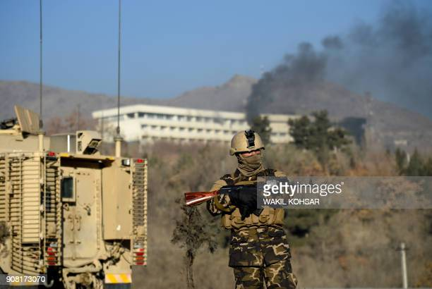 TOPSHOT An Afghan security personnel stands guard as smoke billows from the Intercontinental Hotel during a fight between gunmen and Afghan security...