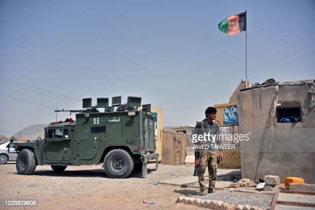 An Afghan security personnel stands guard at the site of a car bomb attack in Kandahar on July 6, 2021.