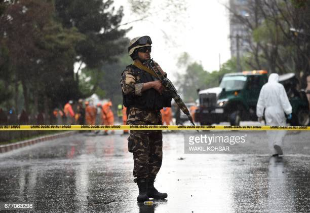 An Afghan security personnel stands guard at the site of a suicide attack that targeted a foreign forces convoy near the US embassy in Kabul on May 3...