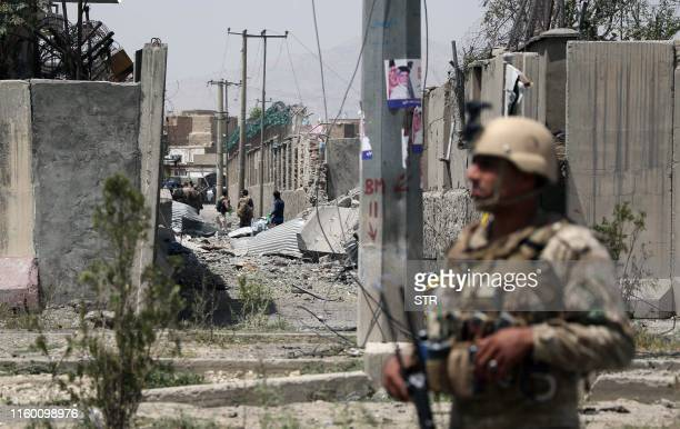 An Afghan security personnel stands guard at the site where a Taliban car bomb detonated at the entrance of a police station in Kabul on August 7...