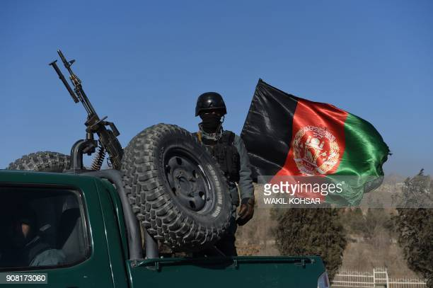 An Afghan security personnel stands guard near the Intercontinental Hotel as ongoing fight between gunmen and Afghan security forces in Kabul on...
