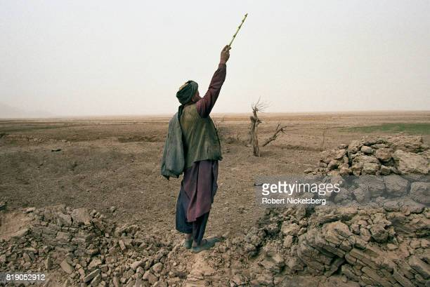 An Afghan shepherd in Chowkar Karez Kandahar province shouts to his children to lead their flock of goats over to him He stands by a wall bombed by...