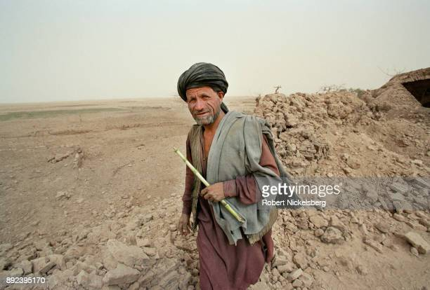 An Afghan shepherd steps over a shattered stone wall in an area bombed by US aircraft November 1, 2001 in Chowkar Karez, Kandahar Province,...