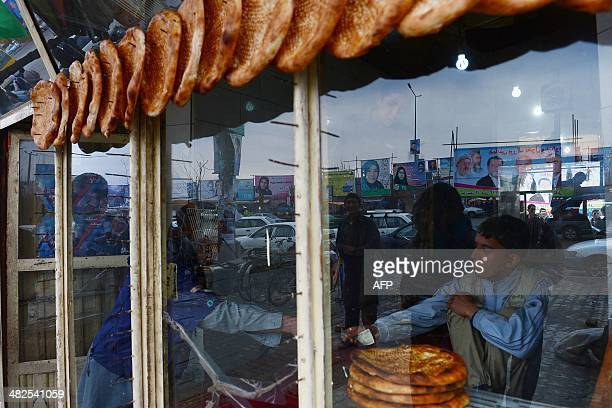 An Afghan shop attendant sells bread in a store as political billboards are reflected in the window in Kabul on April 4 2014 Some 12 million Afghans...