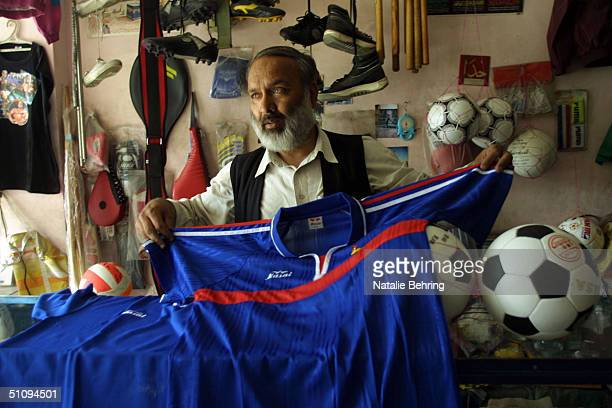 An Afghan Shop Owner Shows Potential Customers A French Football Jersey In His Sports Shop May 30 2002 In Kabul Afghanistan Football Is One Of The...