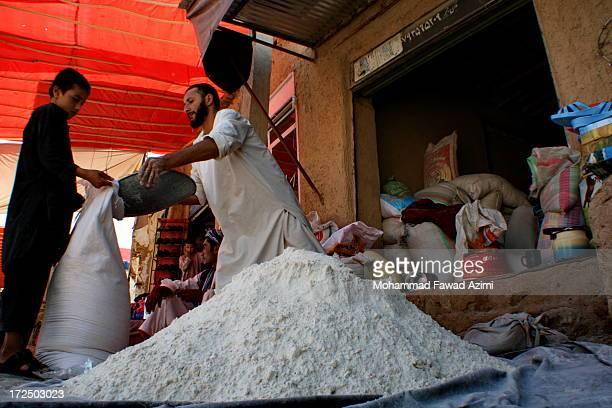 CONTENT] An Afghan shopkeeper selling imported flour in Khulm District of Balkh province in Afghanistan