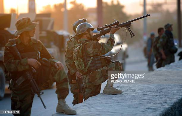An Afghan soldier aims his gun as he guards the area surrounding the Intercontinental hotel during a military operation against Taliban militants...