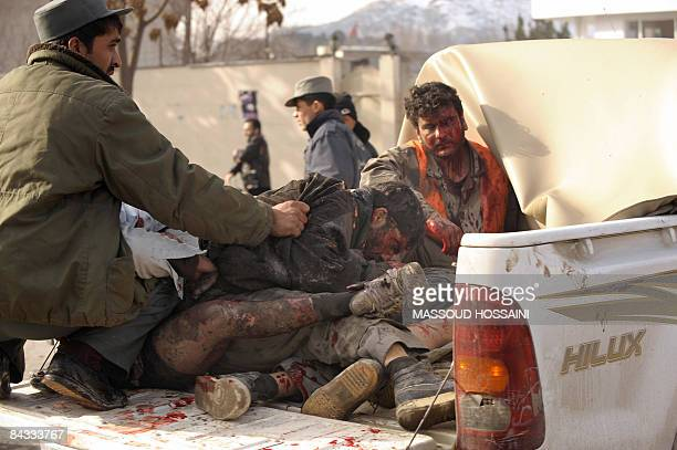 An Afghan soldier helps wounded people onto a pickup truck at the site of a suicide bomb attack in front of the German embassy in Kabul on January 17...