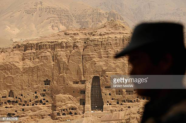 An Afghan soldier keeps watch in front of the empty seat of the Buddha destroyed by the Taliban in Bamiyan on July 7 2008 The cavemonasteries of...