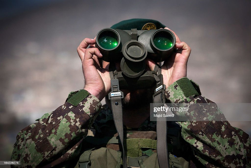 An Afghan soldier keeps watch using his binoculars near the Sakhi shrine, which is the centre of the Afghanistan new year celebrations during the Nowruz festivities on March 21, 2013 in Kabul, Afghanistan. Nowruz is an ancient festival which marks the beginning of the spring equinox and the start of the year in the Iranian calendar, which this coming year will be 1392.