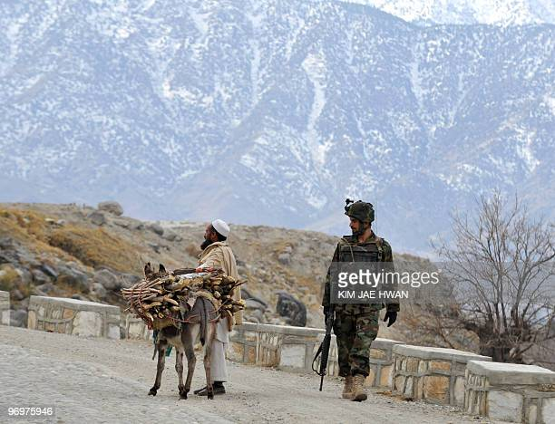 An Afghan soldier looks at an Afghan villager and his donkey carrying wood during a patrol at Gandomak in Langarhar on February 22 2010 US President...