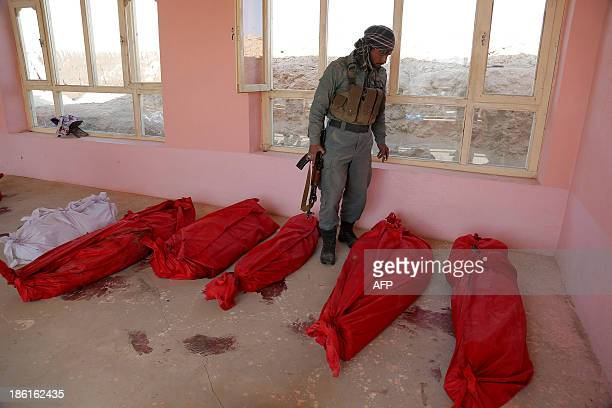 An Afghan soldier looks at the victims of a roadside bomb in the Andar district of the Ghazni province on October 28 2013 A roadside bomb on October...