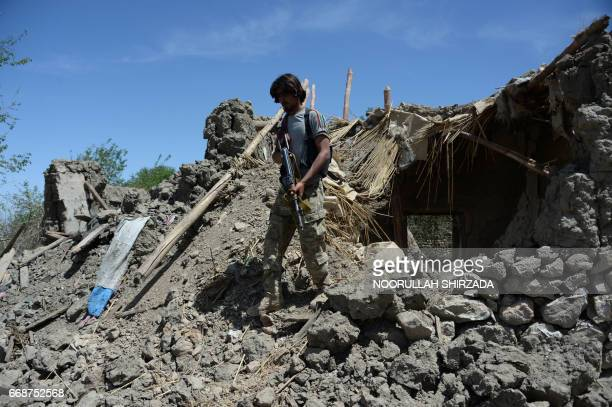 An Afghan soldier patrols near the site of a US bombing during an operation against Islamic State militants in the Achin district of Nangarhar...