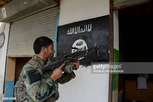 An Afghan soldier points his gun at an Islamic State group banner as he patrols during ongoing clashes in Kot District in eastern Nangarhar province...