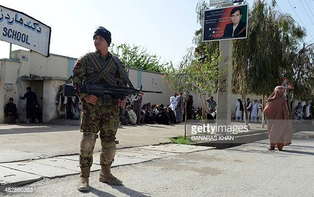 An Afghan soldier stands guard as voters queue outside a local polling station to cast their vote in Kandahar on April 5 2014 Afghan voters went to...