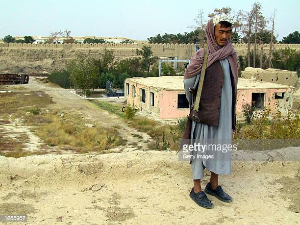 An Afghan soldier stands guard on the Qala Jiangi fortress wall overlooking the memorial to CIA agent Mike Spann and the makeshift prison where he...
