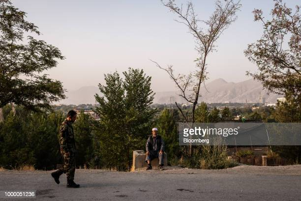An Afghan soldier walks pat a man sitting on the side of the road in the Bibi Mahru Hill area of Kabul Afghanistan on Sunday July 15 2018 US...
