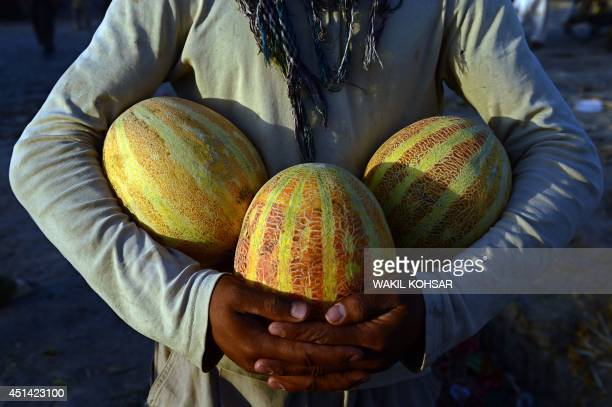 An Afghan street vendor holds melons as he waits for customers at the road side ahead of the Islamic holy month of Ramadan in Kabul on June 28 2014...