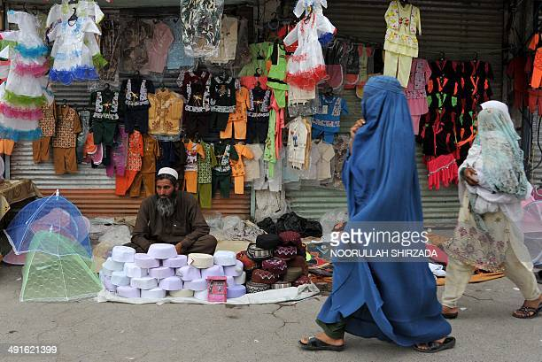 An Afghan street vendor waits for customers as a burqaclad woman walks past on a street in Jalalabad on May 16 2014 Some nine million Afghans or 36...