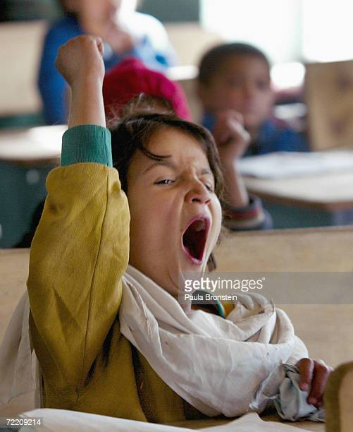 An Afghan student raises her hand as she yawns in the special accelerated learning class February 4 2003 at the Abdul Ghafor Nadim school in Kabul...