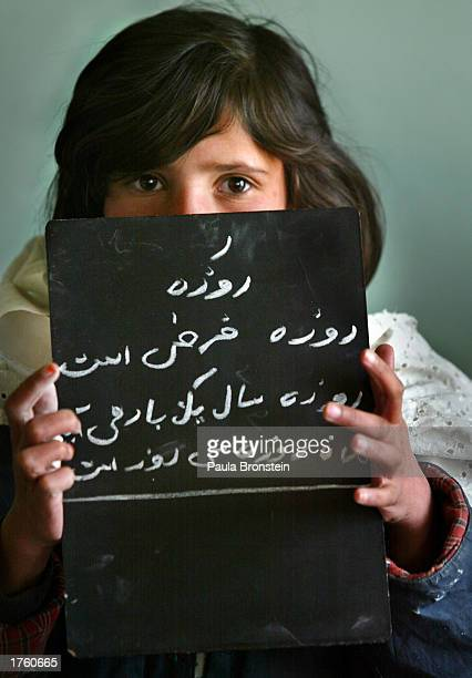 An Afghan student shows her spelling to the teacher during Dari lesson in the special accelerated learning class February 4 2003 at the Abdul Ghafor...