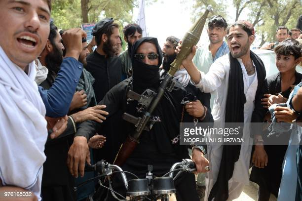 An Afghan Taliban militant carries a rocketpropelled grenade as he looks on with residents as they celebrate a ceasefire on the second day of Eid on...