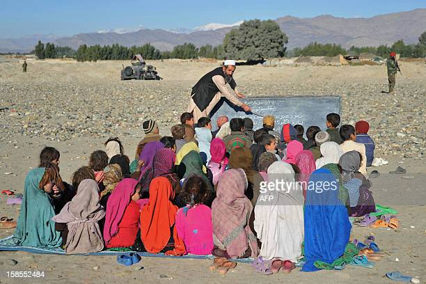 An Afghan teacher holds an outdoor class in the outskirts of Mihtarlam on December 19 2012 Decades of war and conflict in Afghanistan have destroyed...