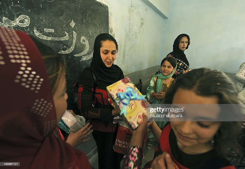 An Afghan teacher receives gifts from her schoolchildren at a school in central Kabul on May 24, 2010, on World Teacher's Day. Afghanistan has been suffering some sort of armed conflict for the past 30 years, starting with the Soviet invasion of 1979, through civil war and, from 1996-2001, rule by the Islamist Taliban who banned girls from education. This has left a huge knowledge gap that the international community has been trying to fill, with billions of dollars of aid pouring in since the Taliban were pushed out in a US-led invasion. AFP PHOTO/Tauseef MUSTAFA