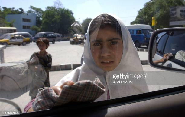 An Afghan teenage girl cleans a window of a car stopped at a traffic intersection in Kabul 04 July 2005 Despite the flood of billions of dollars in...