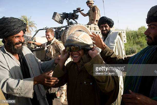 An Afghan teenager play with the helmet of a British Soldier from the Grenadier Guards during a reassurance patrol in a village in a location in the...