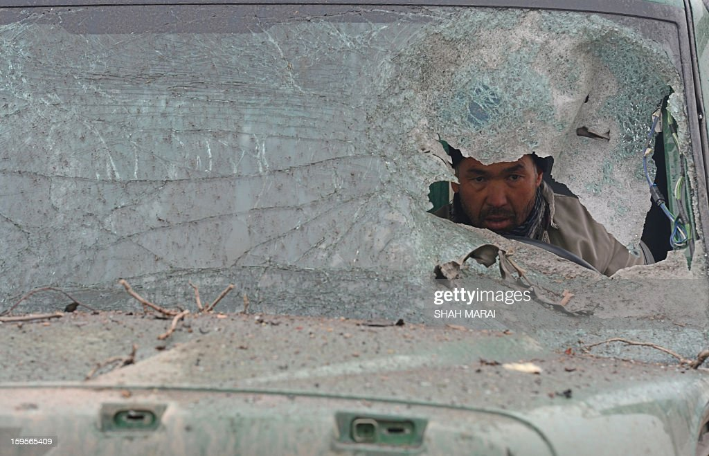 An Afghan truck driver is seen through the broken windshield of his vehicle at the site of a suicide attack near the Afghan intelligence agency headquarters in Kabul on January 16, 2013. A squad of suicide bombers attacked the national intelligence agency headquarters in heavily-fortified central Kabul on January 16, killing at least two guards and wounding dozens of civilians, officials said. AFP PHOTO/ SHAH Marai