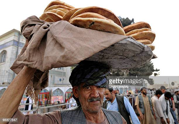 An Afghan vendor carries bread over his head as he waits for customers at a market in Kabul on September 3 during the Muslim holy month of Ramadan...