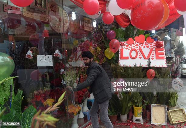 An Afghan vendor decorates the area around his shop with flowers to be sold to celebrate Valentine's Day in Kabul on February 14 2018 In conservative...