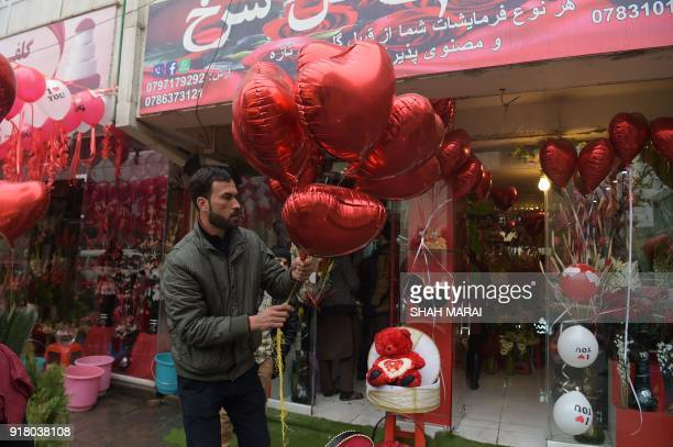 An Afghan vendor holds heartshaped balloons as he decorates the area around his shop with flowers to be sold to celebrate Valentine's Day in Kabul on...