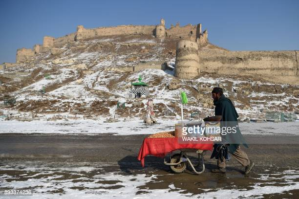 TOPSHOT An Afghan vendor pushes a wheelbarrow after the first snowfall near the old fortress of Bala Hissar in Kabul on December 15 2017 / AFP PHOTO...