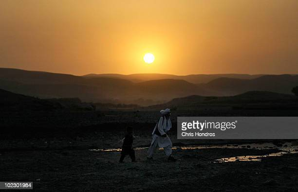 An Afghan villager and a boy traverse a field at dawn June 22 2010 in Khushi Khona Afghanistan in the northern reaches of Herat Province near the...