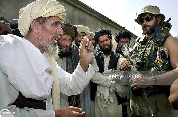 An Afghan villager explains what weapons the local village has to US Army Special Forces Captian 'Goeff' during a search at the Chapman air base...