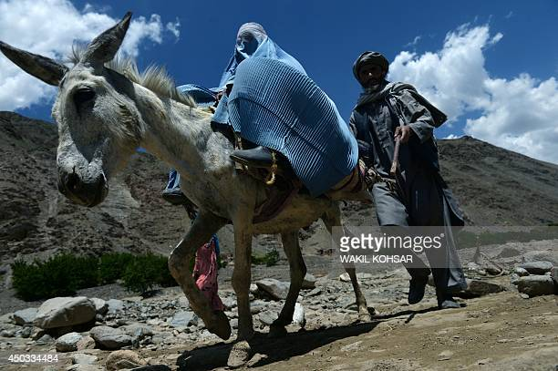 An Afghan villager rides a donkey alongside a pedestrian near the site of a landslide following flooding in the GuzargaheNur district of Baghlan...