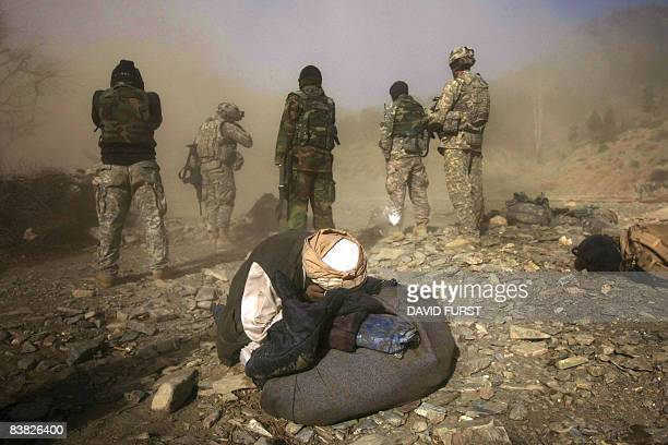 An Afghan villager takes cover from dust and debris from a UH-47 Chinook helicopter landing to pick up US Army soldiers from 2-506 Infantry 101st...