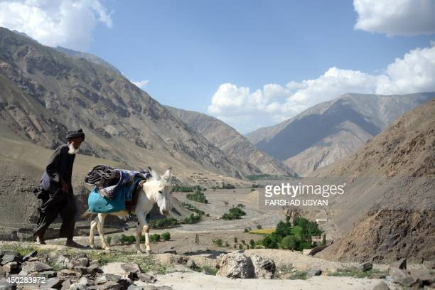 An Afghan villager uses his donkey to carry aid received from the Afghanistan National Army in the Guzirga iNur district of Baghlan province on June...