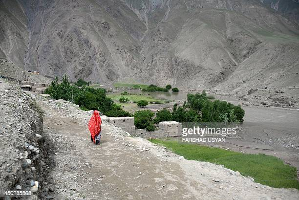 An Afghan villager woman walks to find her family in the Guzirga iNur district of Baghlan province on June 8 2014 Rescuers scrambled Sunday to...