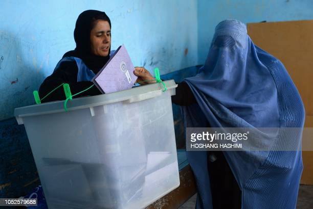 An Afghan voter casts her ballot at a polling centre for the country's legislative election in Herat on October 20 2018 Multiple explosions rocked...