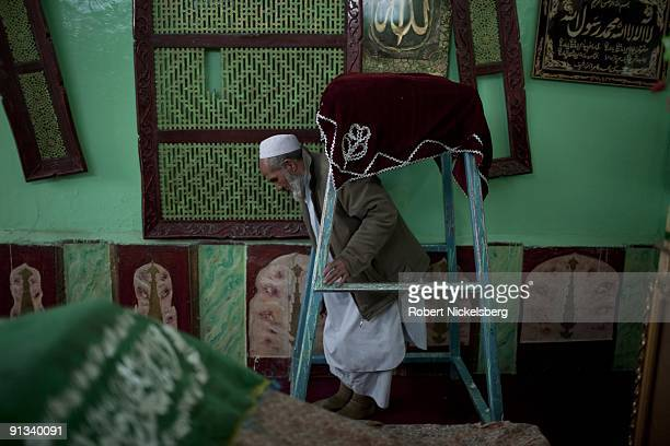 An afghan walks underneath a copy of the Koran in the Asheqan wa Arefan shrine before he offers prayers at the side of Asheq's grave in the old city...