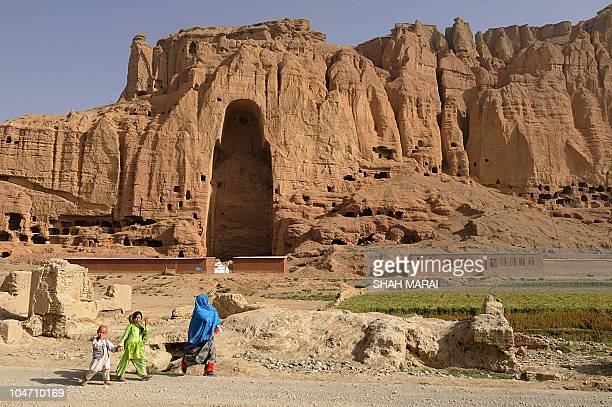 An Afghan woman and children walk past the empty seat of the Buddha destroyed by the Taliban in Bamiyan on July 7 2008 The cavemonasteries of Bamiyan...