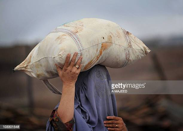 An Afghan woman carries a bag on her head as she evacuates the flooded area of Nowshera on August 8 2010 Fresh rains lashed floodhit Pakistan...