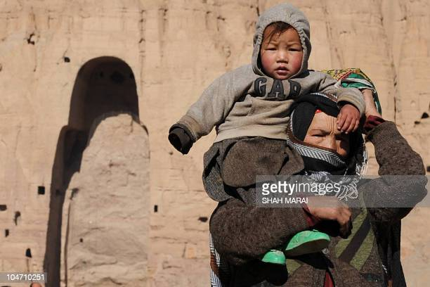 An Afghan woman carrying her son on her shoulder walks past the empty seat of the Buddha statue destroyed by the Taliban in Bamiyan on November 10...