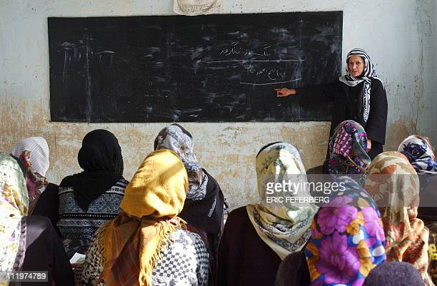 An Afghan woman gives a class to her students 30 January 2002 in a MazareSharif school AFP PHOTO ERIC FEFERBERG